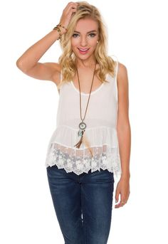 """Details Size Guide Model Stats Contact      Every girl needs a white lace tank in their closet! Our White Sky Lace Top features a semi-sheer, lightweight, loose-fitted fabric with high-low styling, scoop neck front, tank sleeves and bottom lace trim. Stitched waistband with tapered, peplum flair. Wear this graceful top with some dark denim jeans, a pair of tan wedges, a crystal pendant necklace, lots of gold jewelry and some loose waves for a beautiful Spring look. *Rayon blend*34"""" Bu..."""