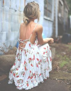 Cute & flirty in this stunning flowy white summer dress with red flower print, spaghetti straps and lace up low back.