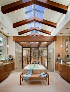 """""""His and hers"""" bathroom with dual showers that look onto a stone fireplace."""
