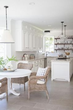 Modern farmhouse kitchen with black and white pendant, Goodman Hanging Lamp, illuminating a round white dining table lined with wicker dining chairs atop a taupe staggered tiled floor by Daltile.