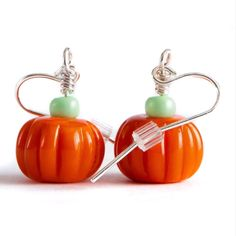 Glass Pumpkin Earrings! Theses are flame worked glass earrings. It is a solid glass pumpkin bead with a little seed bead that looks like the stem of the pumpkin. This is a great teacher gift, or gift for mom. These fall earrings are great if you want to feel festive! Fall fashion, Fall Jewelry, We make everything in Corning NY at The Studio of the Corning Museum of Glass. Small Pumpkins, Glass Pumpkins, Corning Museum Of Glass, Fall Gifts, Halloween Earrings, Great Teacher Gifts, Halloween Accessories, Fall Jewelry, Glass Earrings