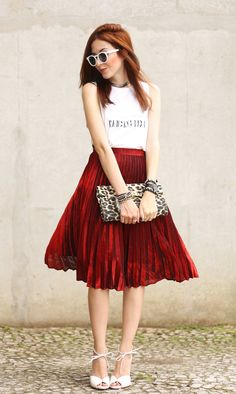 Look super feminino, mas ainda assim não é romântico demais: saia midi plissada vermelha, clutch de oncinha, óculos escuros e camiseta com frase.