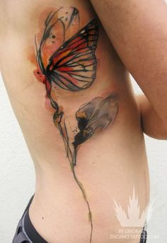 A butterfly clings to a flower stem in this watercolor tattoo by Ondrash