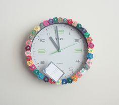 Pronta entrega! <br>Relógio redondo de parede com funcionamento a pilha, visor branco, acrílico, números e detalhes nas cores cinza e verde. Enfeitado com florzinhas de crochê multicoloridas e contas verdes. Poderá decorar e ser útil na copa, cozinha, sala ou corredor.