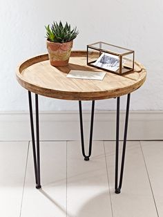 Beautifully carved from mango wood with a natural finish that boasts exposed wood grain details, our simple round table has three hairpin black iron legs. This simple, rustic table is perfect for beside your favourite arm chair and also looks great beside your bed.