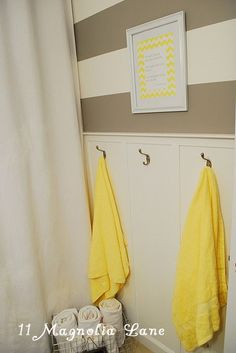 Kids' bathroom decorated with grey horizontal stripes, pops of yellow, and board and batten treatment.  Great for boys or girls (or both!).