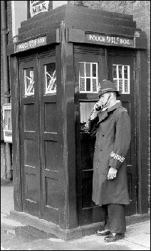 A Metropolitan Policeman using a Police Box. Yes, the Tardis was originally modeled on a real thing that was at the time reasonably familiar on London streets.