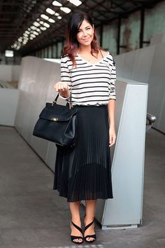 Street style look com saia plissada preta, blusa manga longa listrada e bolsa envelope preta.