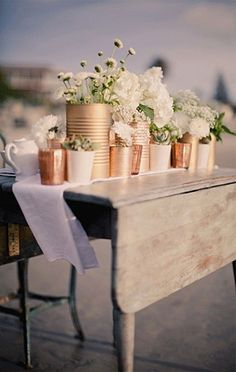 Ordinary tin cans spray painted with metallic spray paint. Perfect for rustic outdoor weddings