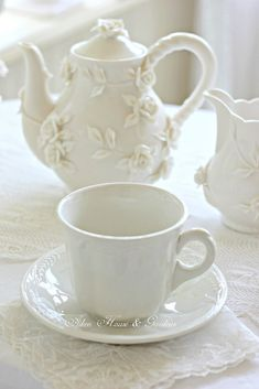 White bas relief pot and creamer with white tea cup and saucer. To broaden the scope and get more use, consider NOT using the lace, and instead doing perhaps a touch of the thin decorative burlap that's so contemporary these days.