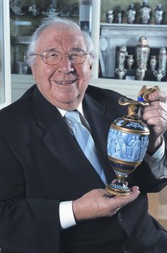 Henry Sandon photographed in the Royal Worcester museum holding the Norman Conquest Ewer painted by Thomas Bott.