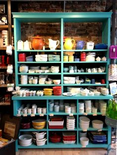 Pop blue shelving against exposed brick wall at Whisk kitchen shop | Favorite Kitchen Shops in NYC
