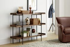Expansive shelving anchors family room, office or kitchen with open styling that puts books and dinnerware on display. Gallery shelves of solid richly grained shesham wood float on a slim open iron frame finished in black.