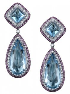 Biscayne Blue Topaz Earrings Inspired by the soft blue and pink hues of twilight, blue topaz tops are accented with white diamonds and pink sapphires which swirl together in lovely pastel shades, while the smooth cabochon cut transparent blue topaz stones glow with delicate tones of pure confectionery bliss