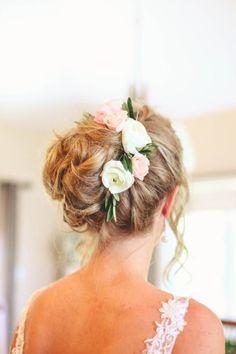 Pelo de la novia en un moño desordenado con flores frescas