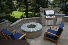 Outdoor mini kitchen with grill and fire pit - love this BUT I would move the firepit away from the retainer wall so more people could sit around the firepit.