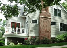 Light gray siding, red brick chimney, black windows with white trim