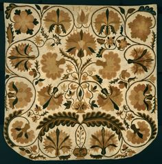 Large tan rug with black and brown floral motif.