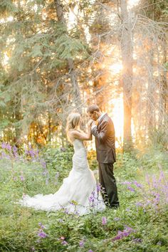 Gorgeous and whimsical bride and groom photo! Love the sunlight shining through in the background. Photo by @kristenbooth
