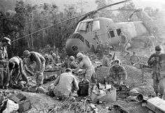 U.S. Marines emerge from their muddy foxholes at sunrise after a third night of fighting against continued attacks of north Vietnamese 324 B division troops during the Vietnam War on Sept. 21, 1966. (AP Photo/Henri Huet)