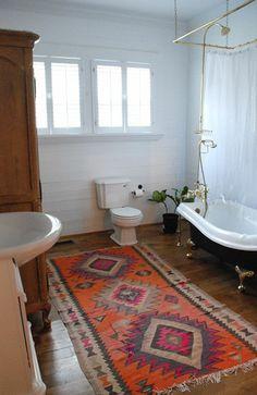 une jolie salle de bain avec planchers en bois foncé et tapis rouge