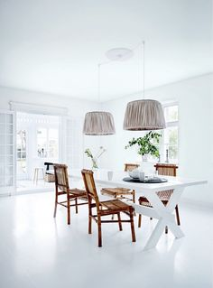 This all white dining space features a white dining table and wooden chairs, as well as fabric pendant lights, and greenery.
