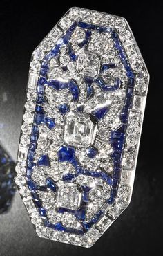 An Art Deco diamond and sapphire brooch, French, circa 1915. Of octagonal form, centring 3 square step-cut diamonds, set within a foliate design of baguette, square and single-cut diamonds, enhanced by calibré-cut sapphires; stamped France, numbered, French assay mark, mounted in platinum; length: 1 7/8in. #ArtDeco #brooch
