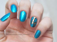 The shimmery blue polish is Tarina Tarantino nail lacquer in Empire and the glittery lightning bolt was done with China Glaze Solar Flare, a gold hex glitter polish.