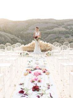 gorgeous Carmel Valley Ranch ceremony space with ghost chairs + flowers alllll down the aisle!