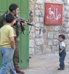 Why would a soldier(idiot) point a gun at a little child? Big man, big gun, little brain.