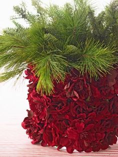 Centerpiece chic  To craft a quick centerpiece, gather evergreen boughs into a container covered in red silk flowers.  Remove stems from silk flowers, and hot-glue blossoms to a cylindrical container. Fill container with water and fresh evergreens.40 Easy Christmas Centerpiece Ideas | Midwest Living