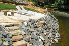 Sandy beach lounging area with cleverly designed fire pit and stone stairway in the shoreline riprap down to the lake.