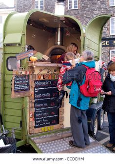 Download this stock image: Street food vendor selling pizza from a converted horse trailer at the Padstow Christmas festival, Cornwall, UK - ECDEHM from Alamy's library of millions of high resolution stock photos, illustrations and vectors.