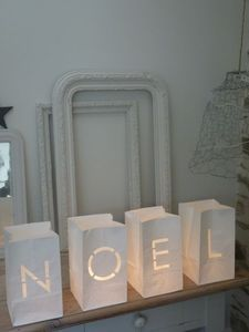 Cut-out lettering - JOY, PEACE, NOEL - from paper bags and place a BATTERY OPERATED votive inside.