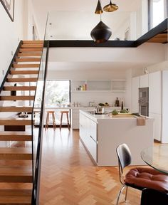 open kitchen space with herringbone floors and an awesome staircase. Love how you can see the upper level.