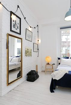 hanging string lights, gilded mirror, white painted brick and floors, vintage pendant. Wow.
