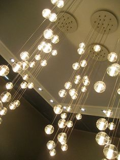 I would suspend the round disks from the ceiling and THEN drop pendants like this...chandelier effect.