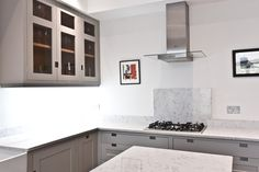 Grey cabinets & white stone worktops create a sophisticated kitchen
