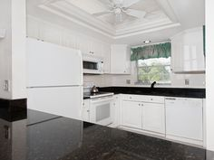 The unit has a bright updated kitchen with a tray ceiling, recessed lighting, high quality white cabinets, and granite countertops. It has neutral tile set on the diagonal, crown molding throughout, and upgraded bathroom vanities.  www.mysanibelrealestate.com