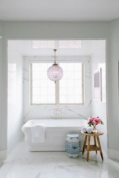 Gorgeous bathroom nook is clad in faux marble tiles by I Marmi di Rex filled with a freestanding tub and a floor mount tub filler placed under window illuminated by a Restoration Hardware 19th C.