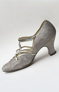"""Silver brocade evening shoes with provenance, c.1923-1927. Made from metallic silver damask woven with a floral pattern of roses. The T-strap and cutwork pattern are silver kid. The complex """"cutwork apron"""" style was the latest word in fashion at the time. The shoes have shapely Louis heels 2 1/2"""" high. The straps close with small silver buttons."""