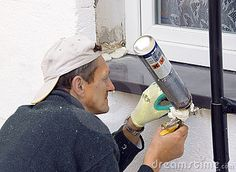 A worker installing a windowsill using a construction foam.  <a href='http://www.dreamstime.com/interiors-rcollection5192-resi208938' STYLE='font-size:13px; text-decoration: blink; color:#FF0000'><b>HOME BUILDING & RENOVATION »</b></a>