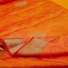 This #sari showcases a half and half pattern with golden yellow on the top and sun-drenched orange in the bottom. The yellow portion is woven with floral thread motifs in maroon, red and blue. Floral and zari motifs are attractively scattered in the orange portion. The elegant gold border is crowned with a liaison of gold leaf motifs while the pallu is a duet in kumkum red and dazzling gold. An offering from #Sarangi's vibrant Kanjivarams. Code 100126446.