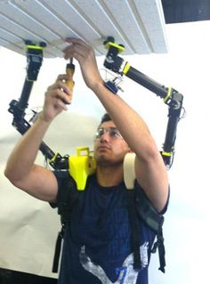 Researcher demonstrates the operation of the robot arms when installing ceiling panels in ...
