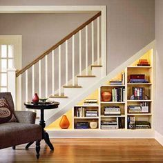 under-stair storage ftw: Lighted built-in shelves hold book overflow from the office, which was made smaller to fit the staircase to the new upstairs rooms.