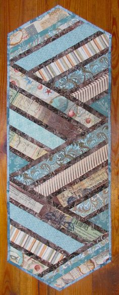 This beach theme quilted table runner is pieced cotton fabrics with a dark brown batik accent and batik double fold binding. Shell prints, blues