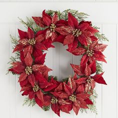 "Known in Mexico as <i>Flor de Noche Buena</i>, or ""Christmas Eve Flower,"" poinsettias are an enduring symbol of the holiday season. So why not use them to welcome guests to your home? Our exclusive wreath is handcrafted from natural twigs, with glittery faux poinsettia leaves, greenery and pinecones. One for every door and mantel should do."