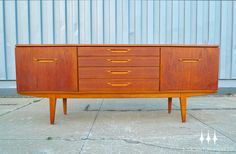 Mid century modern teak credenza by Jentique.  Atomic age inspired pulls add a unique touch to this classic piece.