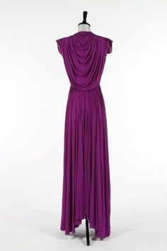 A Madame Grès purple draped silk jersey evening gown, circa 1945, un-labelled, the front bodice with intricate pleats, hook and eye fastening, the bodice back draped in a capelet-like cowl over V-shaped opening,