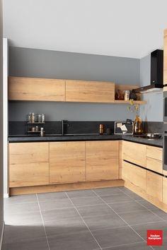 Deze ruime hoekkeuken is volledig uitgerust met houtlook keukenfronten, wat zorgt voor een moderne landelijke stijl. De keuken is afgewerkt met een donker kunststof keukenblad en donkere apparatuur, waaronder een decoratieve afzuigkap, magnetron en oven. Dit geeft deze landelijke keuken een stoere en robuuste uitstraling.